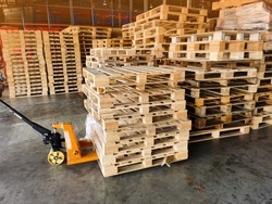Worker driving forklift to loading and unloading wooden pallets from truck to warehouse cargo storage, shipment in logistics and transportation industrial, wood pallets stack