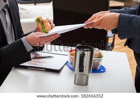 Worker eating lunch in office and getting a task