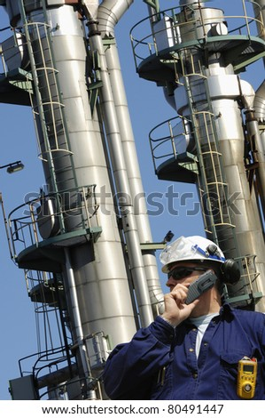 worker, engineer, chemical-worker, standing in front of large refinery oil towers