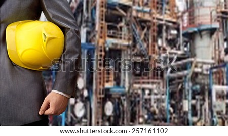 Worker engineer Man work in oil or gas refinery, turning on and off the pipeline valve torso and hand engineer yellow helmet for workers security construction worker No face Unrecognizable person