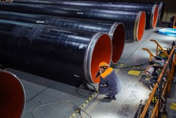 Worker examines new coated pipe in factory.