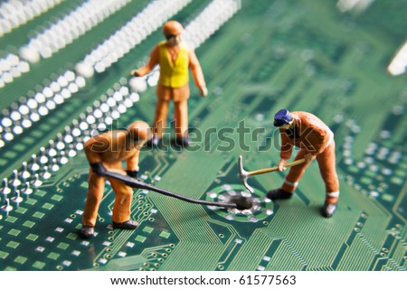 Worker figurines placed on a computer circuit board - stock photo