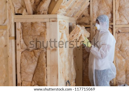 Worker filling walls with insulation material in construction site