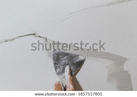 Worker fixing cracks on ceiling, spreading plaster using trowel Stockfoto ©