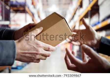 Worker giving a package in distribution warehouse