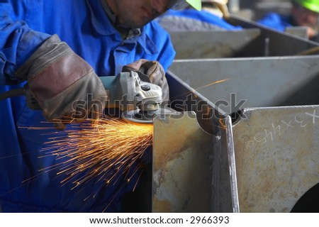 worker grinding, finishing metal, steel