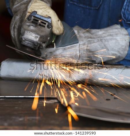 worker grinding steel