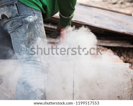 Worker grinds the concrete of angular grinding machine
