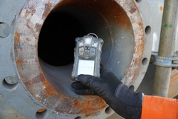 Worker hand holding gas detector device while commencing safety gas testing atmosphere at manhole to work construction site
