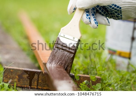 Worker Hand Paint Metallic Rusty Pipe In His Brush With Brown Paint Outdoor Close Up. #1048476715
