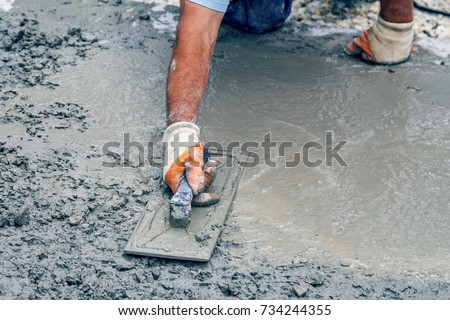 Worker hand with trowel leveling concrete, spreading poured. Vintage style.