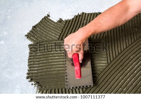 Worker hand with trowel tool for tiles installation making mortar adhesive on floor