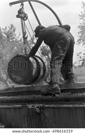 Worker handling barrel of asphalt during road construction