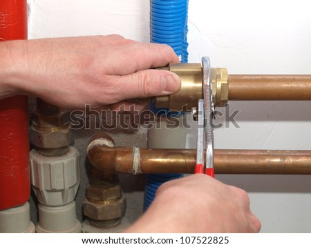 Worker hands fixing heating system with a special tool
