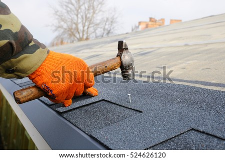 Worker hands installing bitumen roof shingles. Worker Hammer in Nails on the Roof. Roofer is hammering a Nail in the Roof Shingles. Construction Nails Vapor barrier and Waterproofing. Unfinished roof.