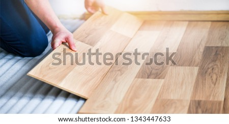 Worker hands installing timber laminate floor. Wooden floors house renovation with measure items. Stok fotoğraf ©