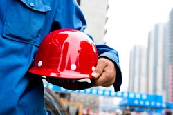 Worker holding a helmet with background of  blurred construction site.