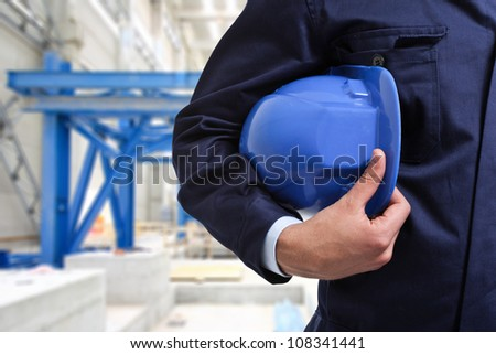 Worker holding an helmet in a construction site