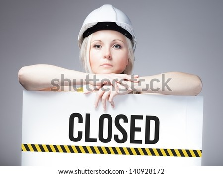 Worker holding closed sign placed on information board