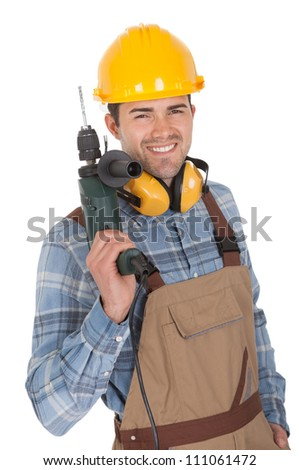 Worker holding electric drill and wearing hard hat. Isolated on white