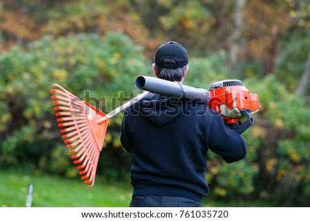 Worker holding leaf blower and rake