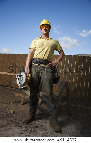 Worker in a hardhat and safety glasses stands at a construction site with a hand on his hip. He holds a circular saw with the other hand. Vertical shot.