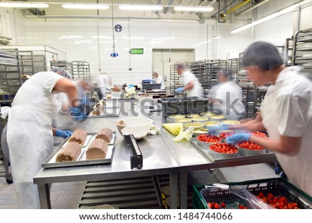 Worker in a large bakery - industrial production of bakery products on an assembly line