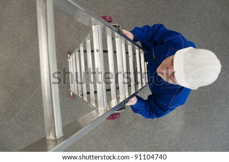 worker in a white helmet, enters the ladder