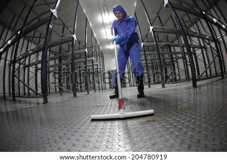 worker in blue protective uniform cleaning floor in empty storehouse fish eye lens