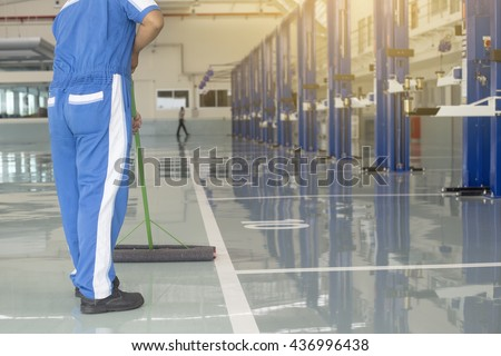 worker in blue, protective uniform cleaning new epoxy floor in empty storehouse or car service center