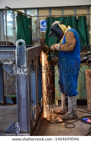 Worker in blue uniform, safety shoes, leather gloves, welding mask. He is standing and grinding the welded of workpiece with an electric grinder.