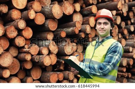 Worker in helmet counts wood lumber Stock photo ©