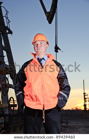 Worker in orange uniform and helmet on of background the pump jack and sunset sky. Severe. Hands in pockets.