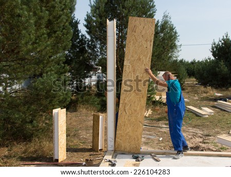 Worker in overalls standing erecting insulated wooden wall panels on a building site of a new house