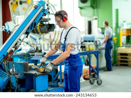 worker in protective clothing in factory using machine