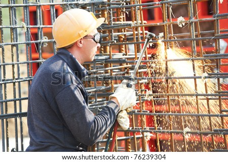 worker in protective glasses cutting concrete reinforcing metal rods at construction building site - stock photo