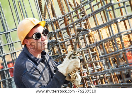 worker in protective glasses cutting concrete reinforcing metal rods at construction building site