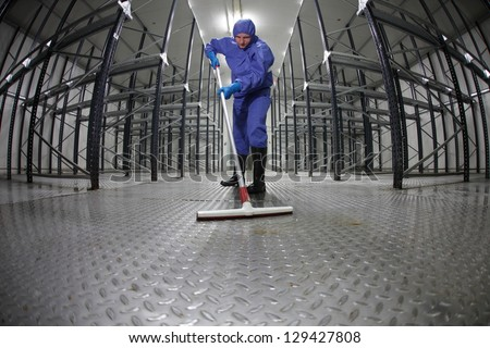 worker in protective overalls cleaning floor in empty storehouse - fish-eye lens