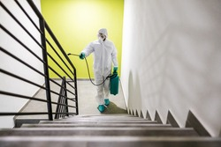Worker in protective suit and mask sterilizing railing in building from corona virus / covid- 19.