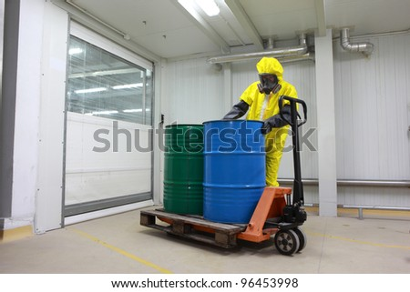 Worker in protective uniform,mask,gloves and boots  working with barrels of chemicals on forklift