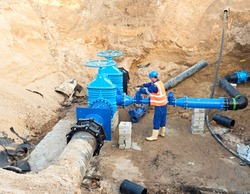 Worker in protective workwear underground on gate valve, reconstrucion of drink water system