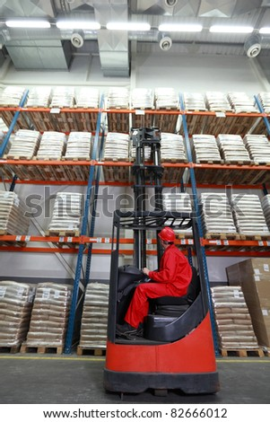 Worker in red uniform and safety helmet loading sacks with forklift loader in warehouse
