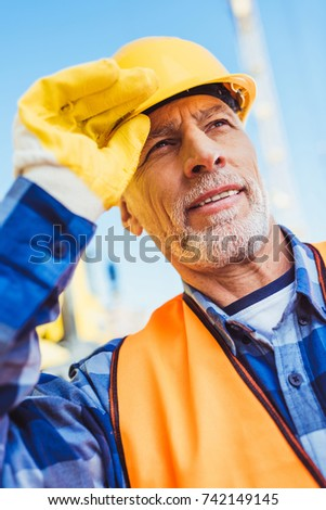 Worker in reflective vest and hardhat at construction site