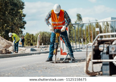 Worker in reflective vest with drill repairing street during roadworks stock photo