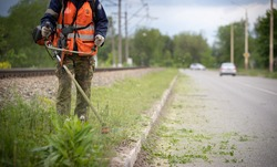 Worker in special protective reflective clothing with a lawn mower in his hands, mows grass with dandelions next to the road and railway tracks. Trimmer in the hands of a man. Cars in the background.