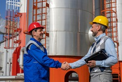 Worker in Uniform and Businessperson Shaking Hands Against Power Plant or Oil Refinery Storage Tanks. Worker in Personal Protective Equipment Meeting with Businessperson. Teamwork Concept.
