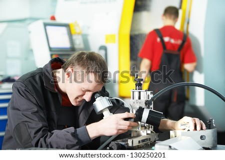 worker in uniform checking quality of processed tool using precise optical device