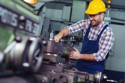 Worker in uniform operating in manual lathe in metal industry factory.