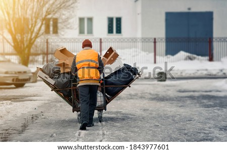 Worker in uniform rolling pushing cart of garbages, paper, carton, cardboard boxes, plastic bags with waste to recycling collection area. Man rolling trolley with garbage and debris to disposal  Foto d'archivio ©