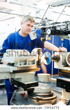 worker in uniform working on sharpening machine tool